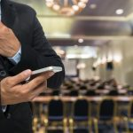 Businessman using the smart phone on the Abstract blurred photo of conference hall or seminar room background